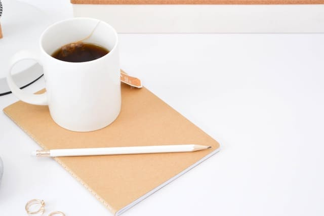 bloggers make money selling ebooks, tea, cup on the desk, notebook