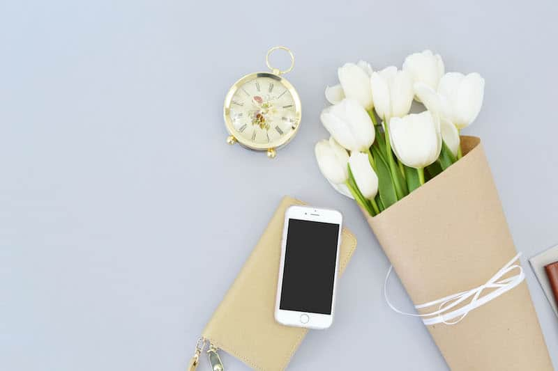 clock and flowers on the desktop for time management tips
