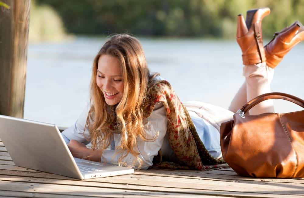 Is blogging income passive? Woman working on laptop in a scenic view